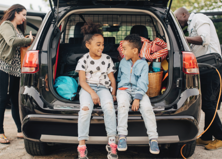 family loading car for trip with kids in the center