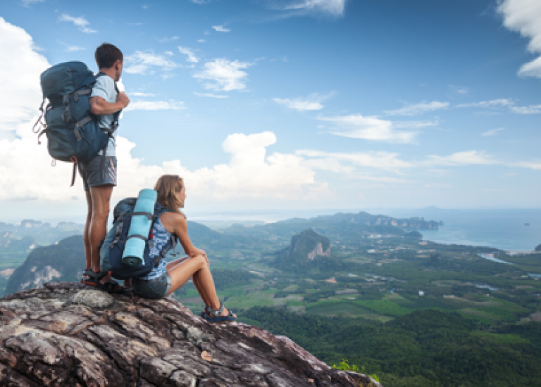 woman and man sitting on mountain staring at scenery