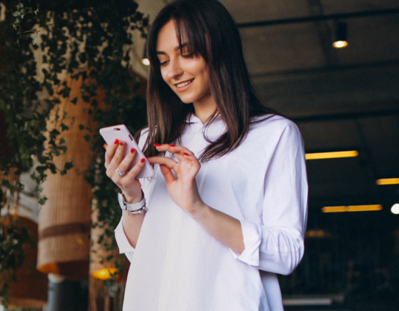 woman smiling while looking at phone